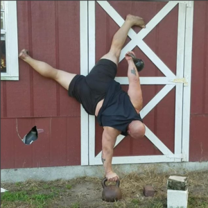 Bud Jeffries doing a one arm handstand on a kettlebell