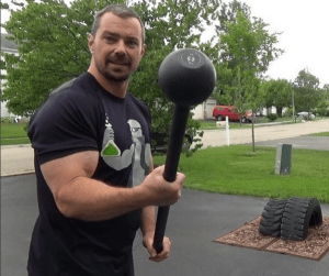 Nick Nilsson holding a mace outside his home