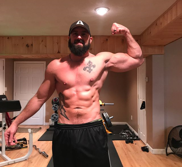 home gym dad Paul Walsworth flexing in his basement gym