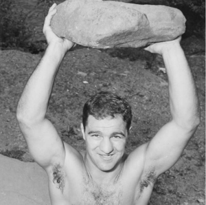 Rocky Marciano holding a stone overhead