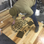 adding decals to a lifting platform at North Street Strength in Granby, MA