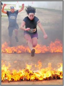 Julie Beck jumping over fire at an Obstacle Course Race