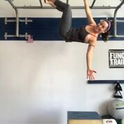 MovNat coach Julie Beck of Warrior Up Fitness doing a single arm hang