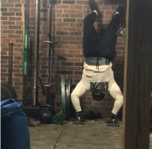 strongman competitor Brian Pankey doing handstand pushups in his backyard gym