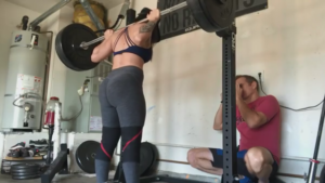 Powerlifter Yolanda Presswood sets up to squat while her husband, Steven, takes a candid photo