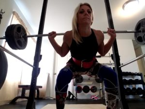 Heidi King doing squats in her garage gym