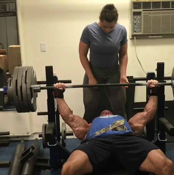 stan efferding bench pressing with his wife in his garage gym