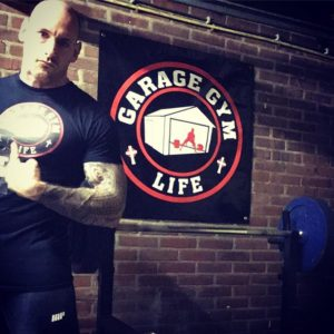 Tim Geurts posing in front of a Garage Gym Life Logo Wall poster