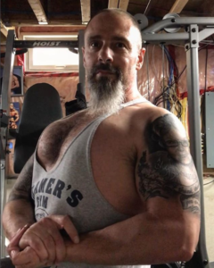 Heart attack survivor Rich Dlin hits a side chest pose in his basement gym